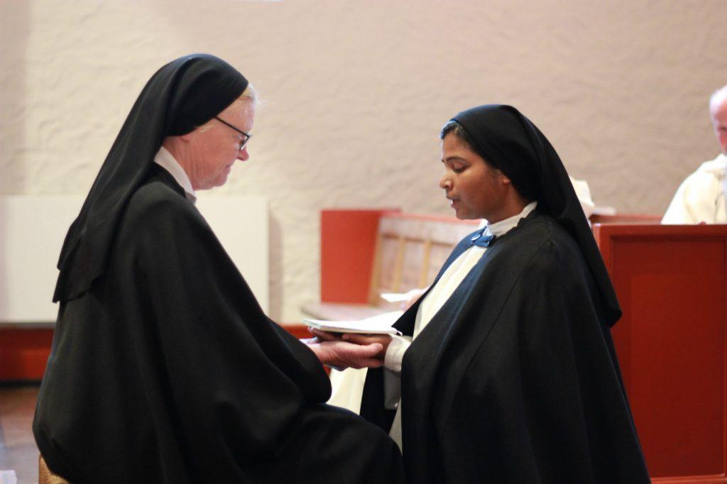 Bilde av sr. Sheeba som knelende og med sine hender i generalpriorinnens hender avlegger sitt første klosterløfte.